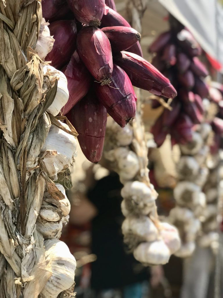 Fresh garlic and onions at a roadside stand.